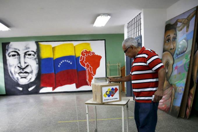 Homem deposita seu voto em frente a mural com a figura do ex-presidente Hugo Chávez em escola de Caracas, na Venezuela (Foto: Carlos Garcia Rawlins/Reuters)
