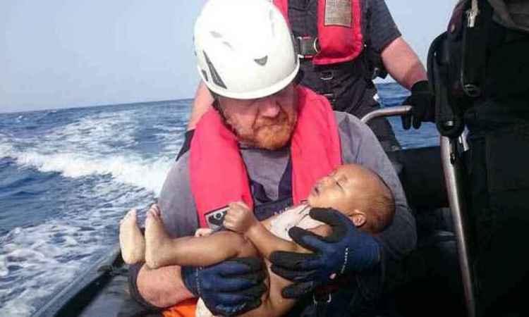 Martin, voluntário da organização Sea-Watch, segura o corpo da criança: gesto instintivo de proteção - Foto: Christian Büttner/Eikon Nord Gmbh Germany)