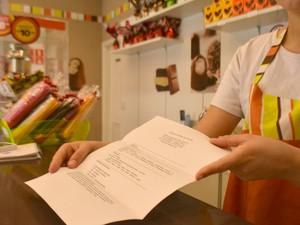 Funcionária recebe currículo para trabalho em loja, em Campinas (SP) (Foto: Clara Rios/G1)