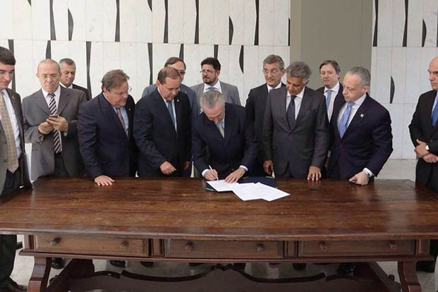 Michel Temer, ao lado de alguns dos seus futuros ministros, assina notificação de posse como presidente encaminhada pelo Senado. (Foto: Twitter Oficial/Michel Temer)