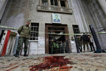 Forças de segurança sírias se reúnem sob um retrato do presidente Bashar Assad no antigo palácio de justiça em Damasco, após um atentado suicida - 15/03/2017 (Louai Beshara/AFP)